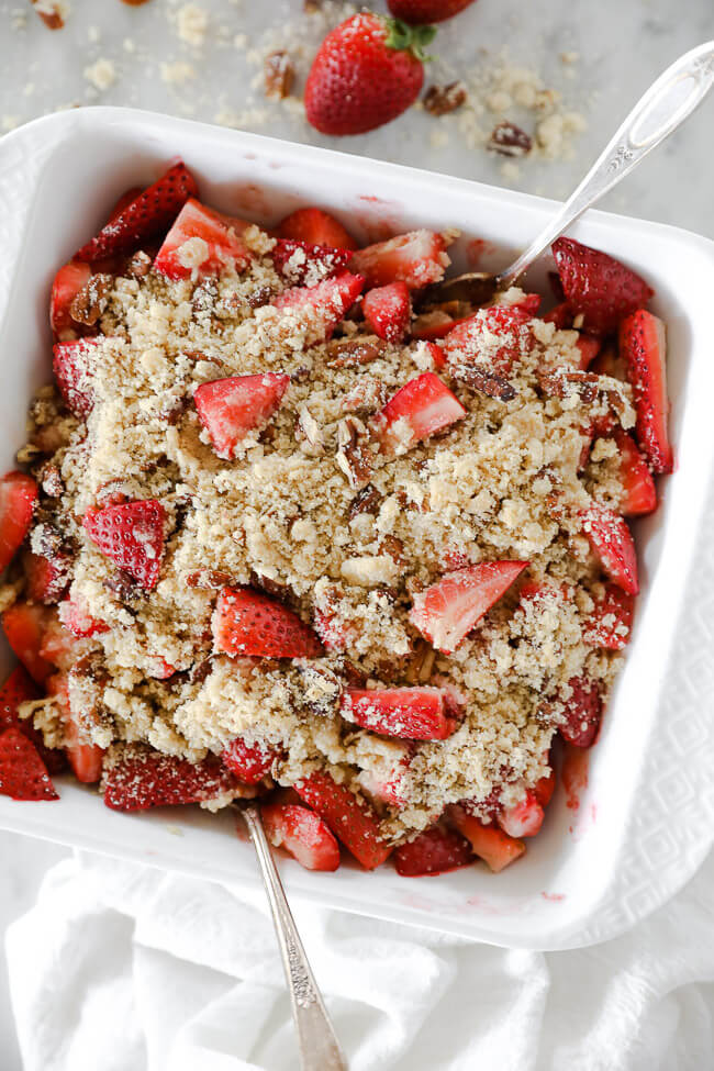Vertical overhead image of baked strawberry crumble in baking dish with two spoons dug in.