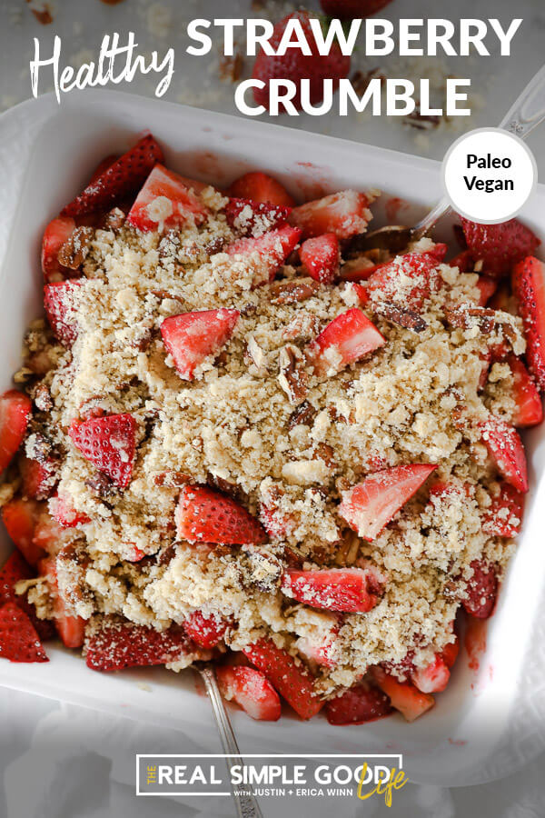 """Vertical overhead image with text overlay at top that says """"Healthy Strawberry Crumble - Paleo + Vegan"""". Image of crumble in baking dish with two spoons dug in."""
