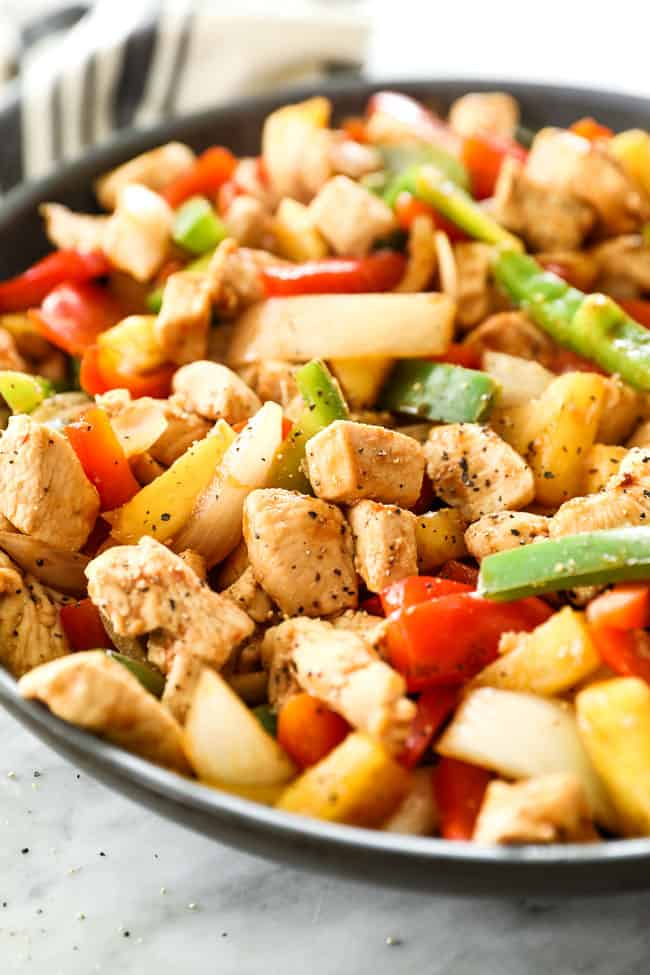 Angled shot of healthy sweet and sour chicken in a skillet. Dish includes chicken, onion, red and green bell pepper, pineapple and a sweet and sour sauce.
