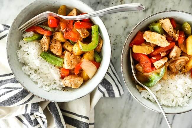 Overhead shot of healthy sweet and sour chicken served up in two bowls with white rice and forks dug into bowls.