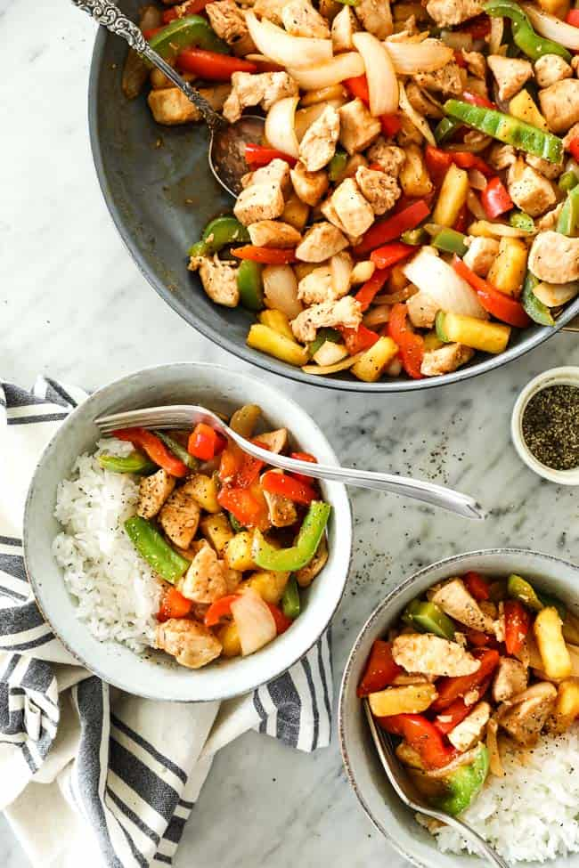 Overhead shot of healthy sweet and sour chicken in skillet with serving spoon and served up in two bowls with white rice.