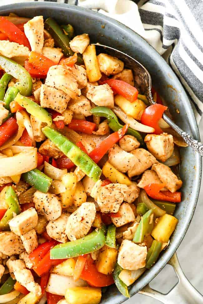 Overhead close up shot of healthy sweet and sour chicken in skillet with serving spoon. Dish includes chicken, onion, red and green bell pepper, pineapple and a sweet and sour sauce.