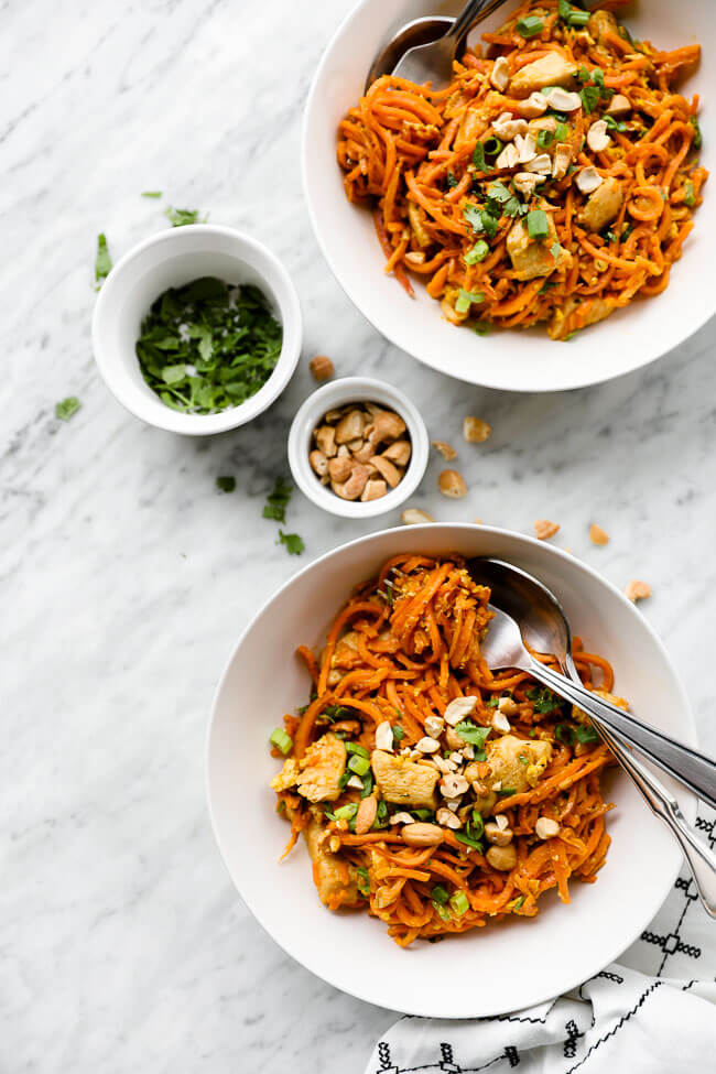 Vertical overhead image of healthy sweet potato pad thai recipe in two bowls with extra cilantro and chopped cashews on the side. Sweet potato noodles are swirled around a fork in one bowl.