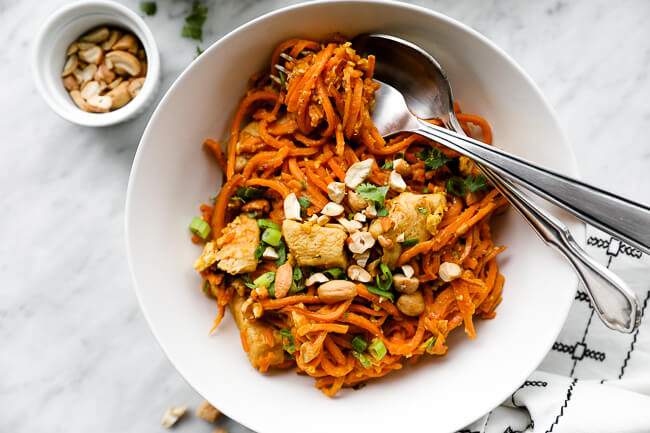 Horizontal overhead image of healthy sweet potato pad thai recipe in a bowl with noodles swirled around a fork.