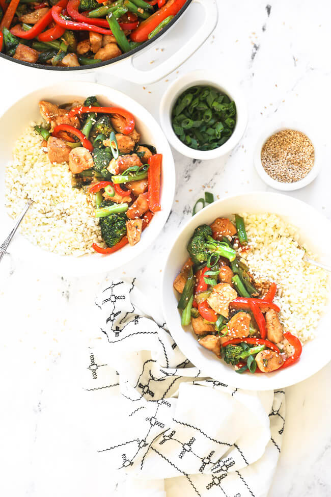 Overhead image of teriyaki chicken stir fry served up in two bowls with cauliflower rice.