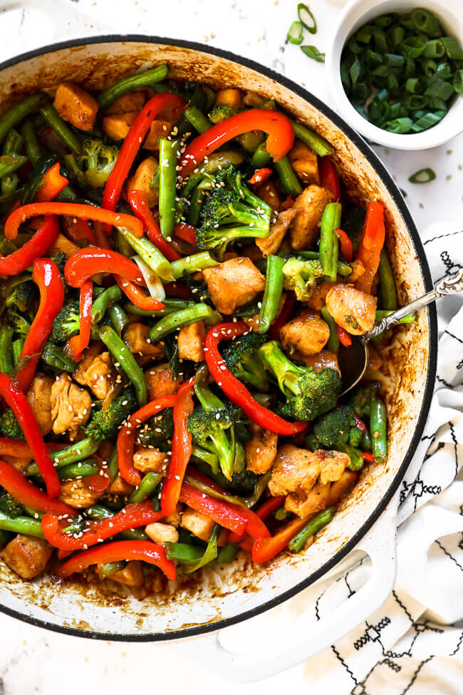 Close up overhead image of healthy teriyaki chicken in a skillet with a serving spoon scooped in.