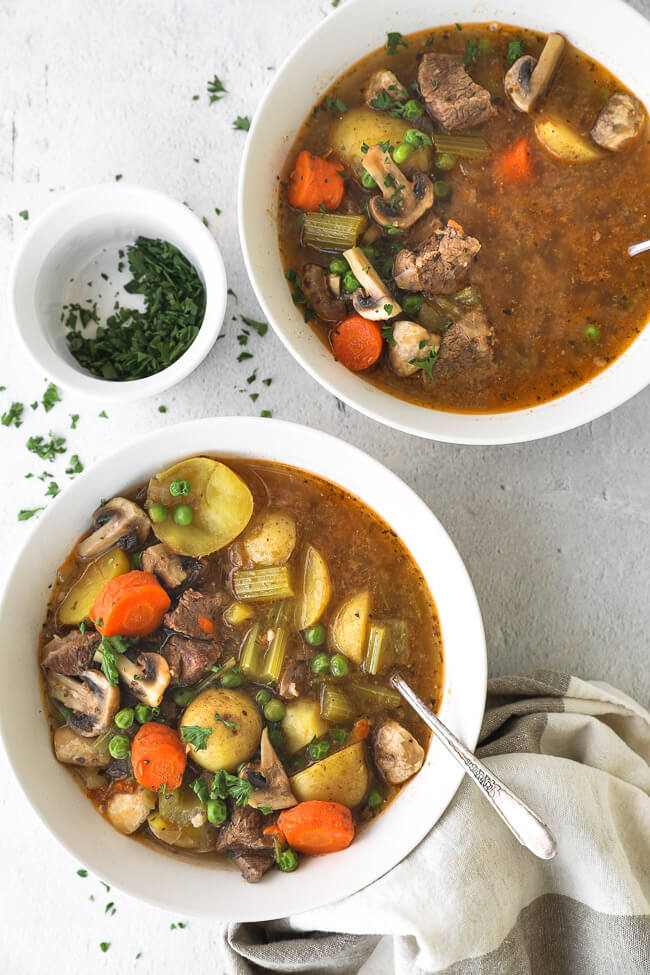Two bowls filled with hearty beef soup with vegetables