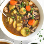 Overhead close up of hearty instant pot beef and vegetable soup with potatoes, carrots, celery mushrooms and peas