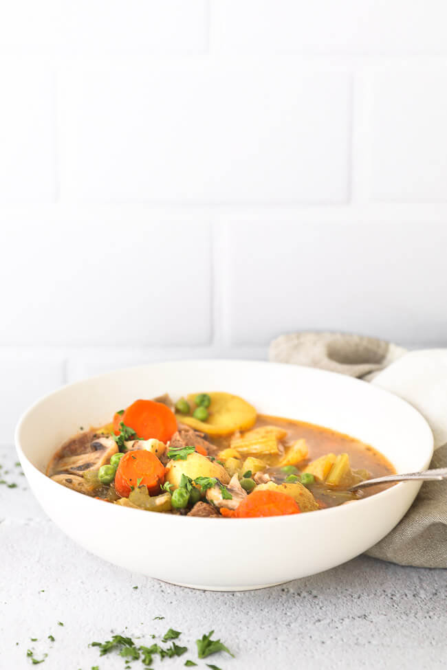 Straight on shot of bowl filled with soup of beef, carrots celery, mushrooms and peas