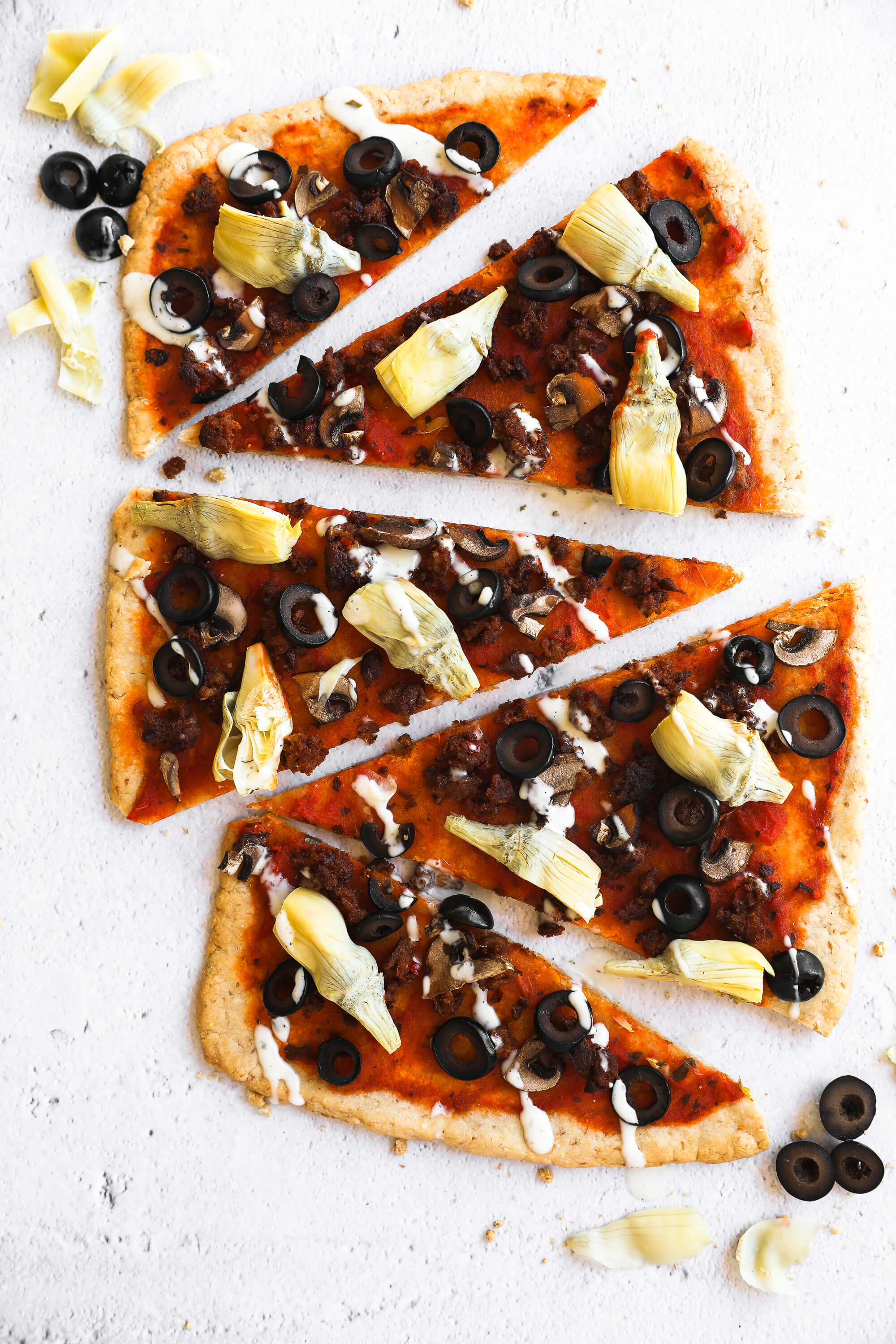 Gluten free flatbread pizza cut into slices and lined up vertically with ranch drizzled on top.