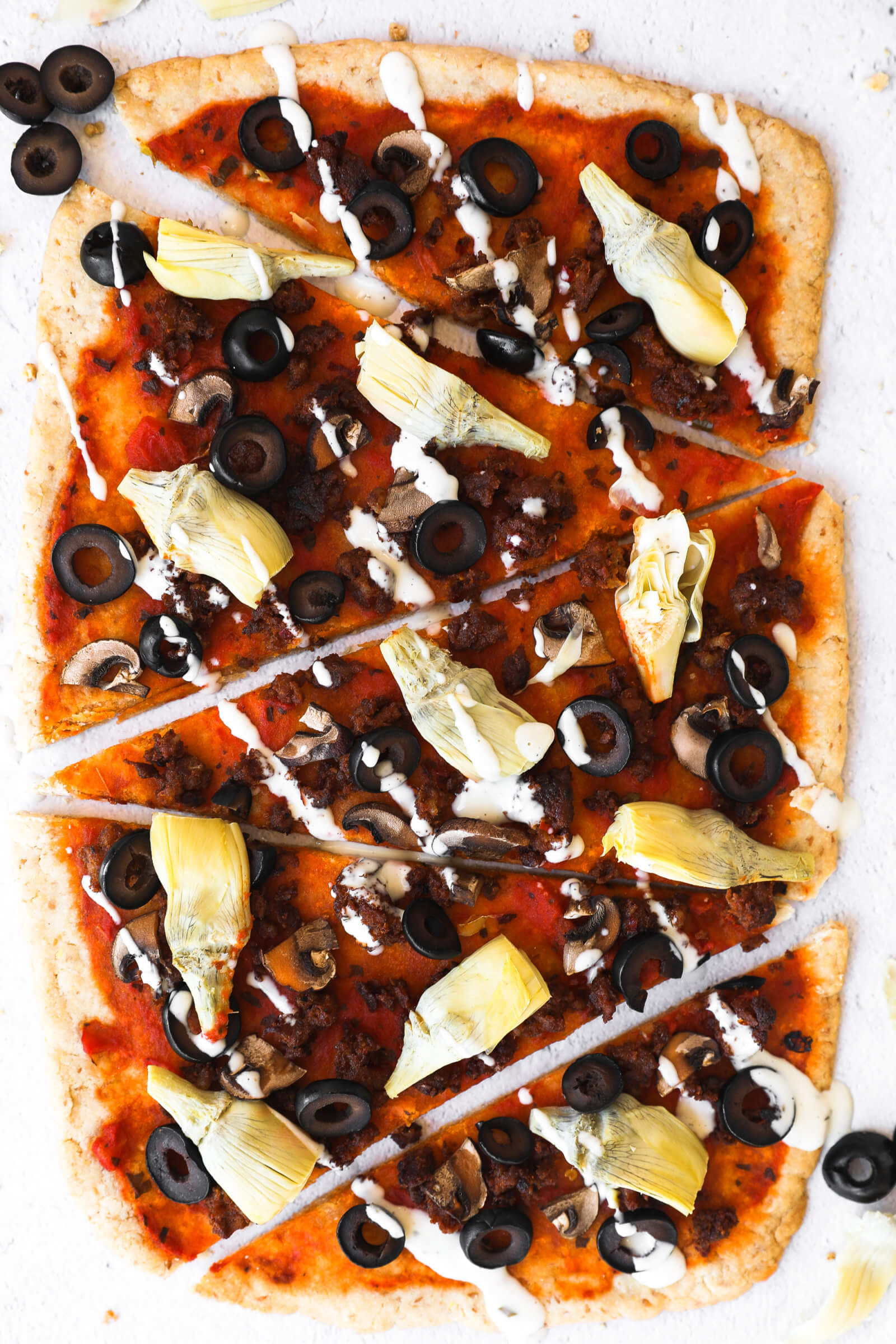 Homemade gluten free flatbread pizza sliced into pieces and drizzled with ranch. Pieces are lined up vertically.