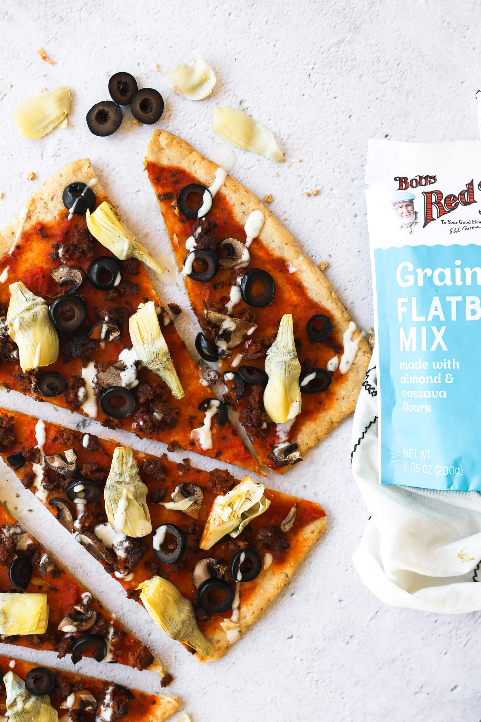 Flatbread pizza slices with a package of Bobs Red Mill Grain Free Flatbread Mix.