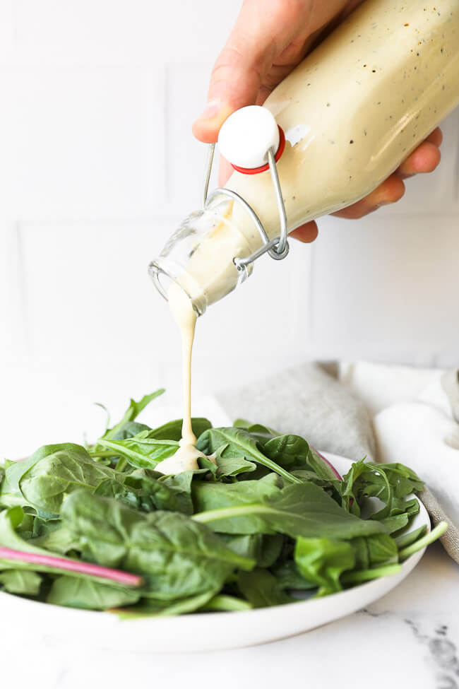 Image of pouring keto caesar dressing onto a plate of greens.