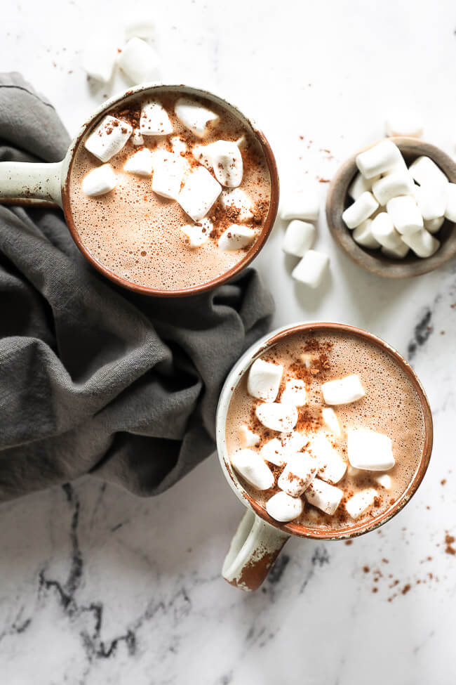Overhead image of two mugs of vegan hot chocolate with marshmallows and cocoa powder on top.