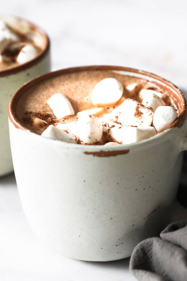 Close up angled image of a mug of dairy free hot cocoa with marshmallows and cocoa powder sprinkled on top.