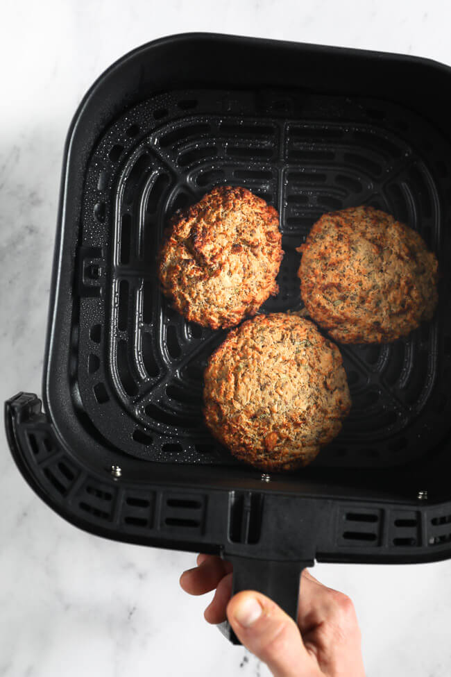 Three cooked salmon patties in an air fryer basket with hand holding basket