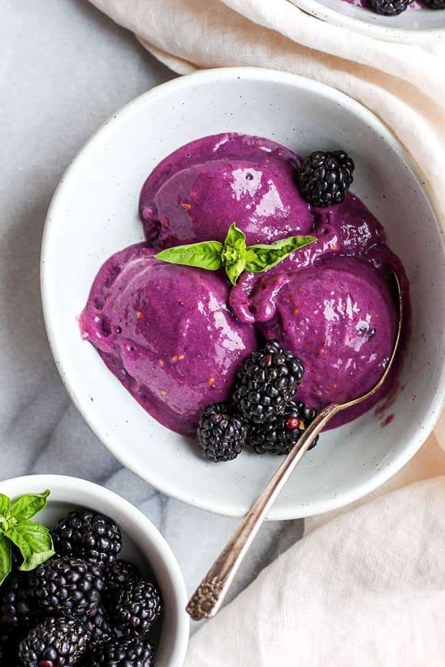 Three scoops of blackberry basil ice cream in a bowl with basil leaf in middle