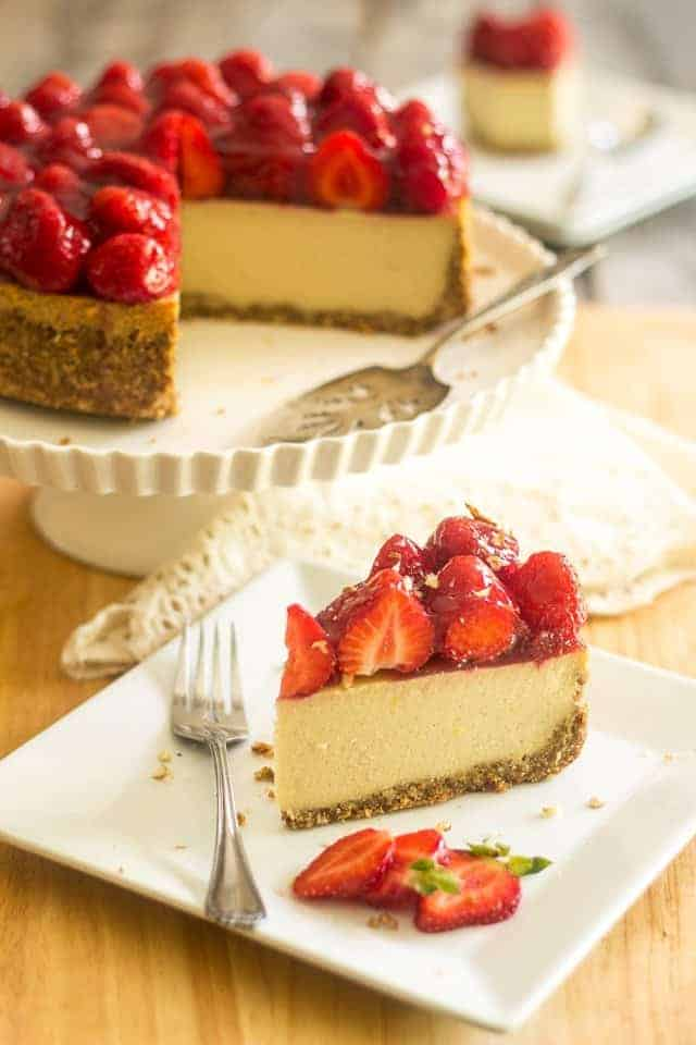 Strawberry cheesecake slice on a plate with fork. Cake in background on a platter.