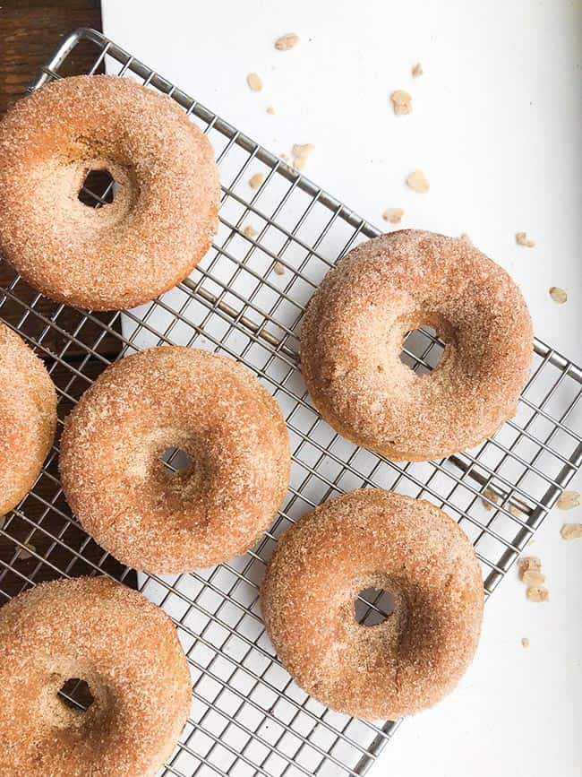 Gingerbread donuts on a cooling rack with sugar dusting