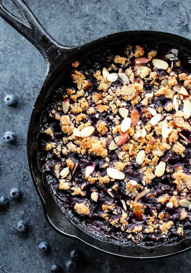 Overhead of blueberry cobbler in a cast iron skillet with nuts on top
