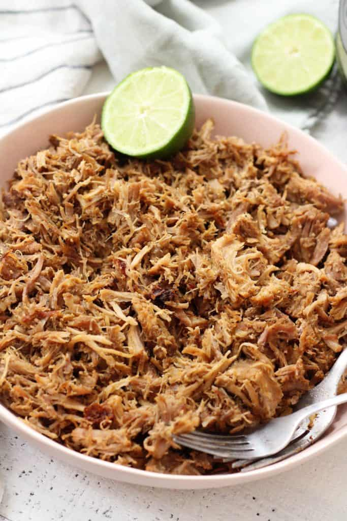 Carnitas shredded in a bowl with lime