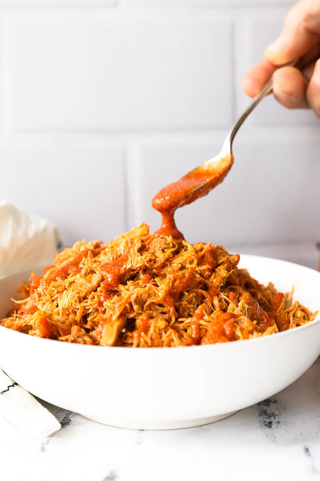 Shredded buffalo chicken in a bowl with sauce pouring in from a spoon