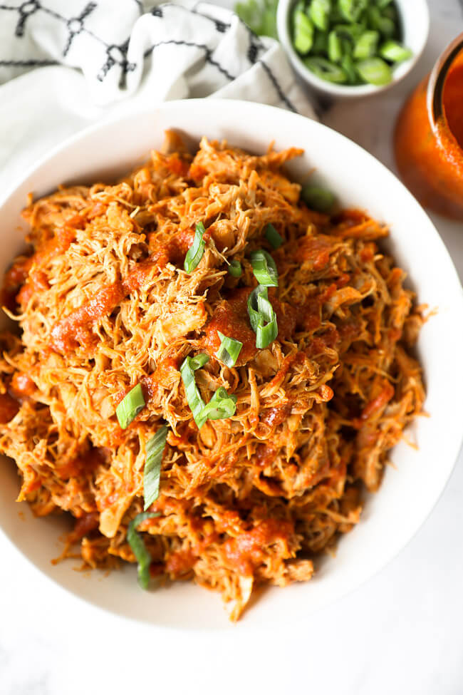 Instant pot buffalo chicken shredded in a bowl with sliced green onions on top