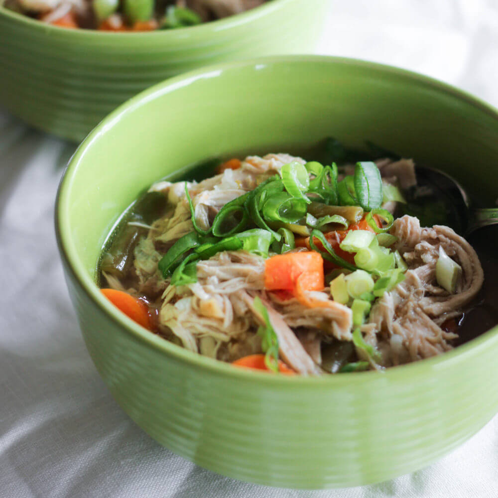Shredded chicken soup in a green bowl with carrots and green onions