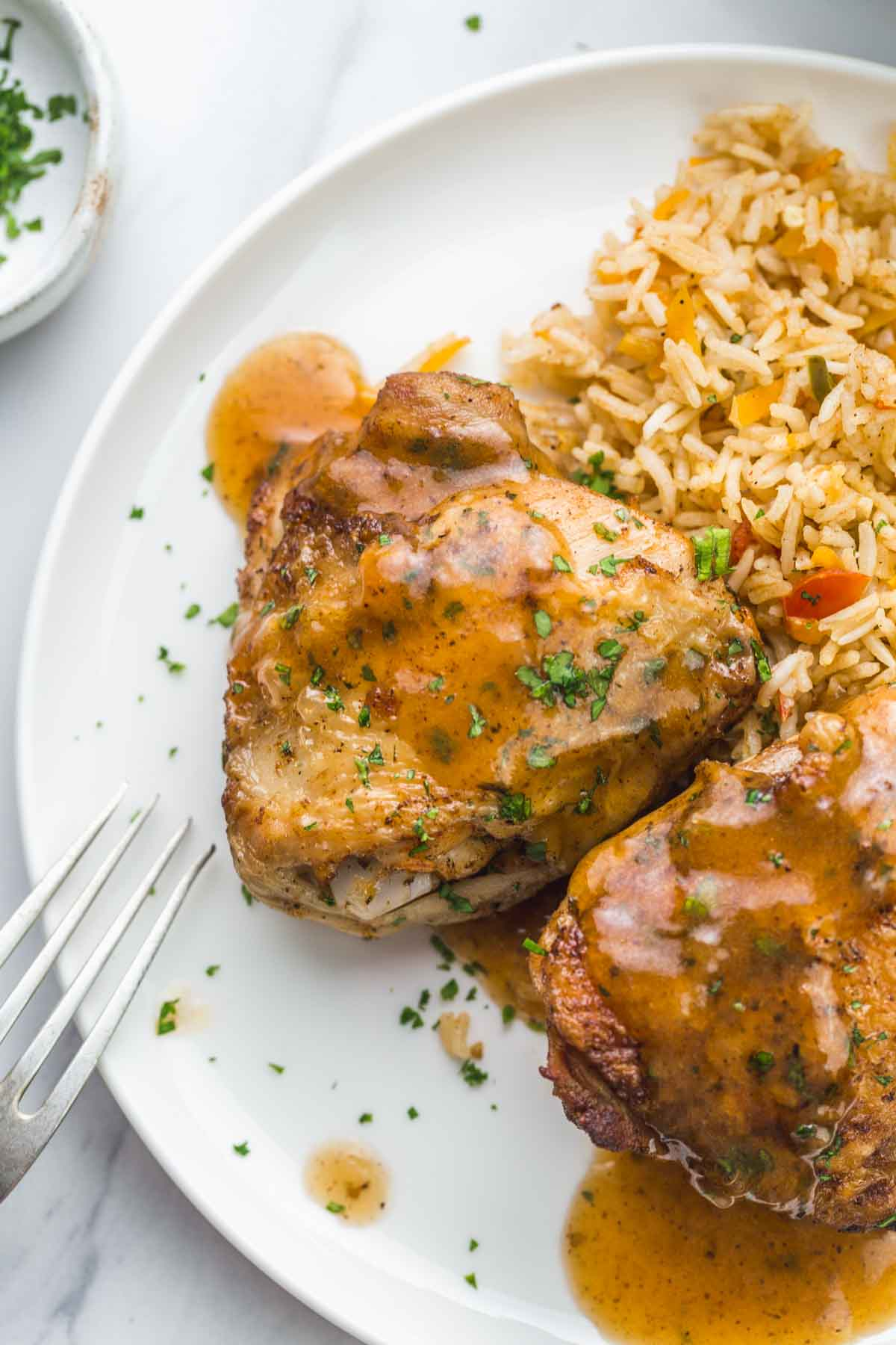 Skin on chicken thighs on a white plate with rice and gravy