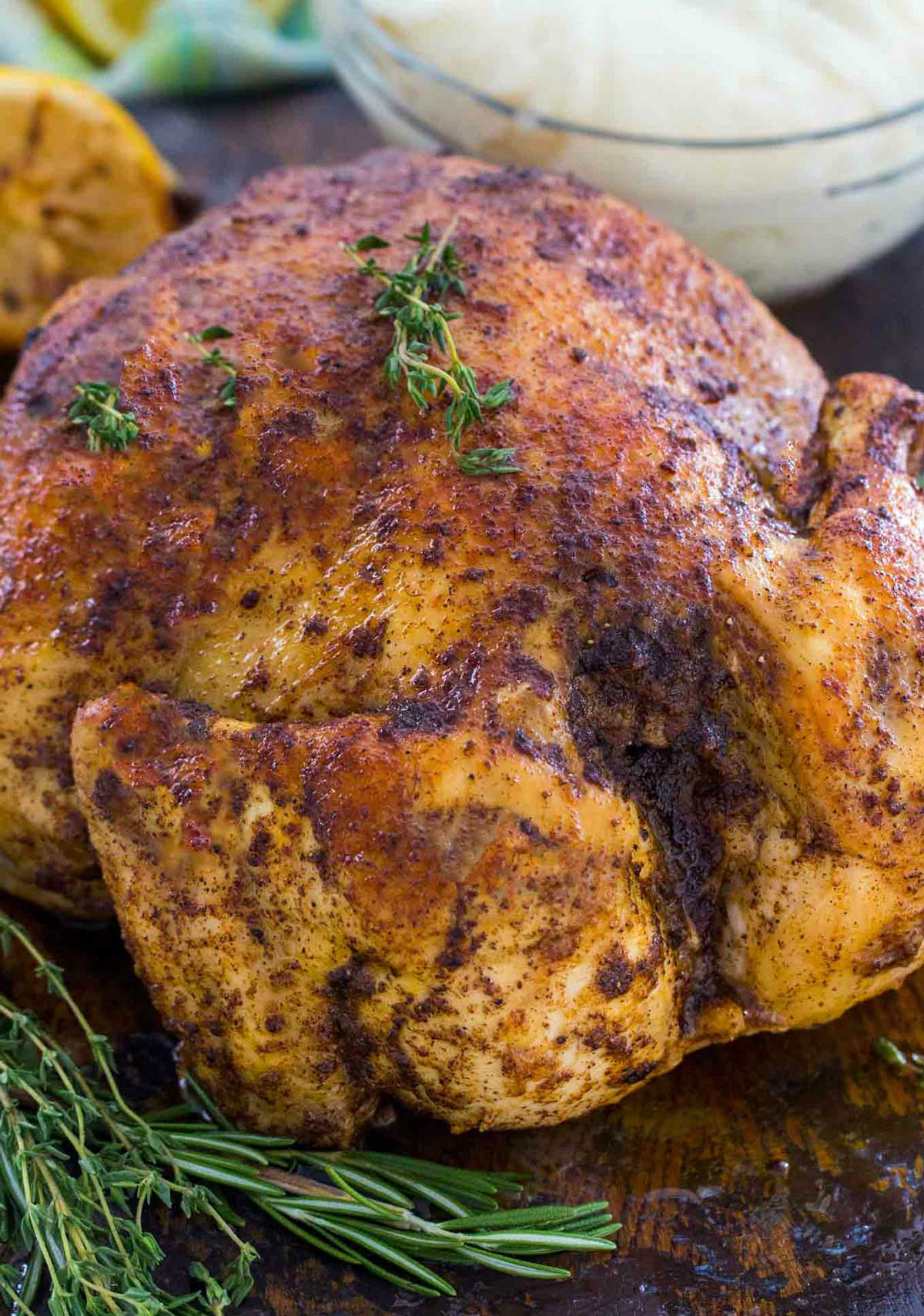 Whole cooked chicken on a board with rosemary sprigs