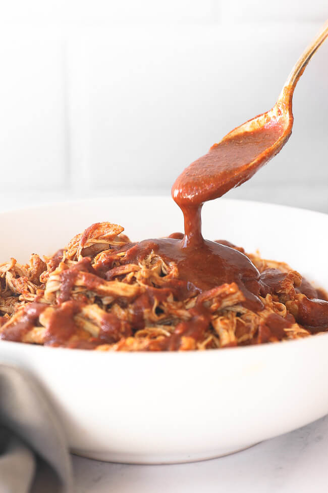 Instant pot BBQ shredded chicken in a bowl with a spoon pouring BBQ sauce on top