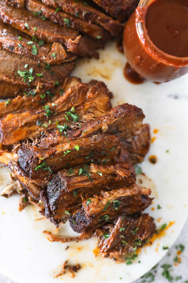 Instant pot beef brisket sliced on a board with BBQ in s jar on the side close up vertical image