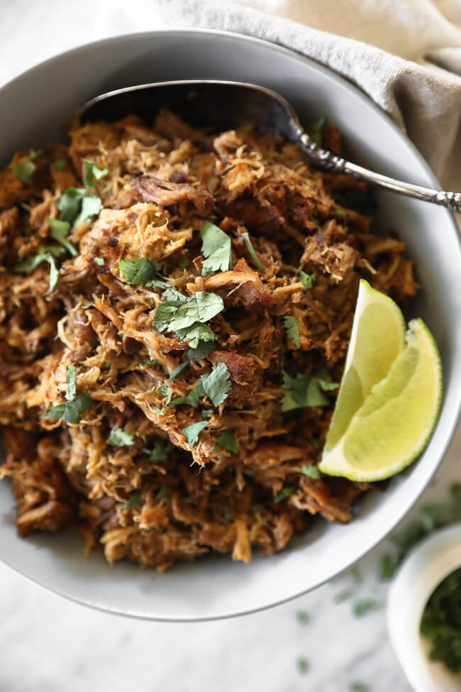 Instant pot carnitas in bowl with lime wedges and cilantro overhead vertical close up image