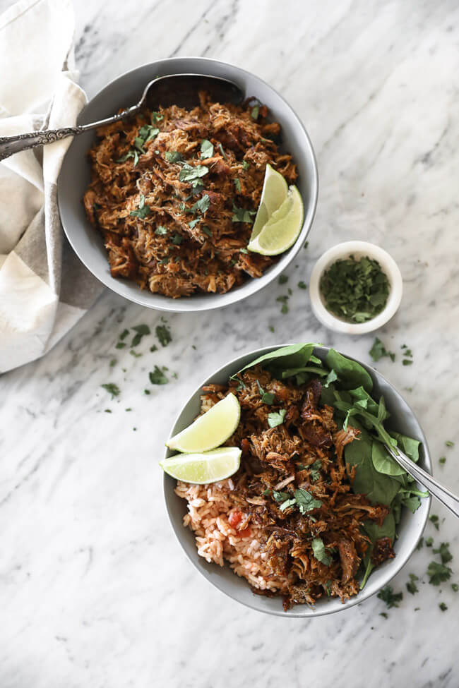Instant pot carnitas in bowls with lime wedges, cilantro, rice and spinach overhead vertical image