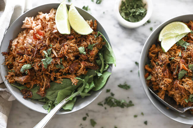 Instant pot carnitas in bowls with rice and spinach horizontal overhead image