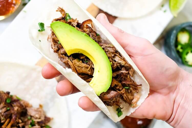 Hand holding a taco with avocado slice on top