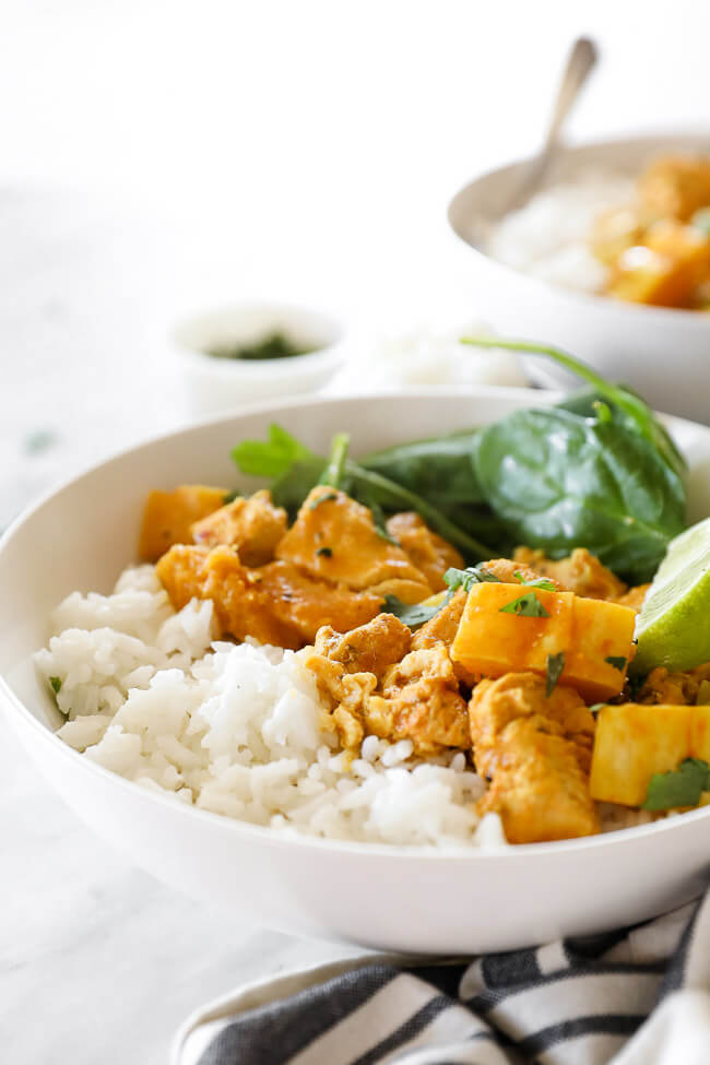 Instant pot chicken curry in bowl with rice, spinach and rice close up vertical image at angle