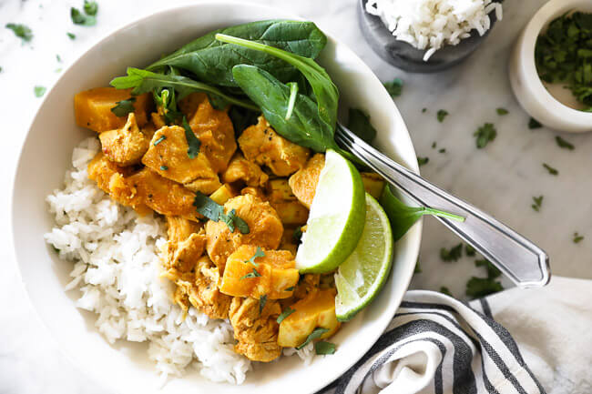 Instant pot chicken curry in bowl with rice, spinach and lime horizontal image