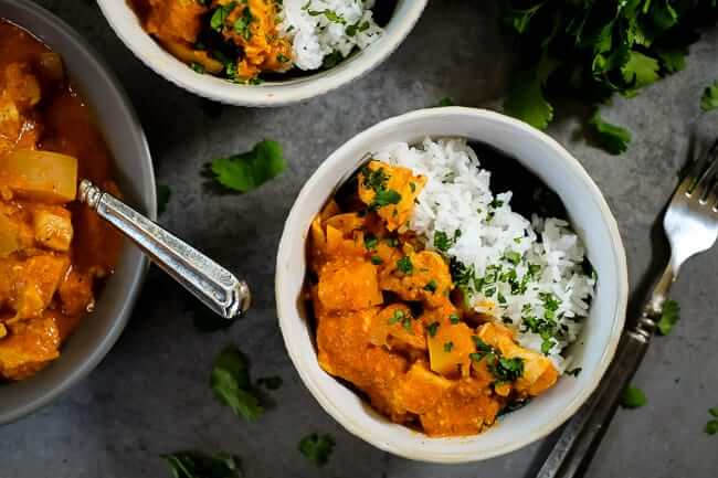 Instant pot chicken curry with white rice and cilantro garnish.