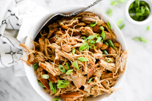 Horizontal image of instant pot honey garlic chicken in a bowl with a serving spoon, topped with chopped green onion.