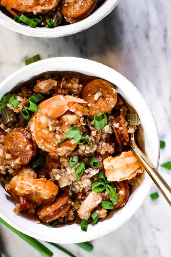 Instant pot jambalaya served in a couple bowls with chopped green onion garnish and forks.