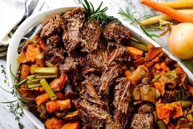 Instant Pot pot roast on a serving platter with sweet potato, carrots, onion, celery and fresh herbs.