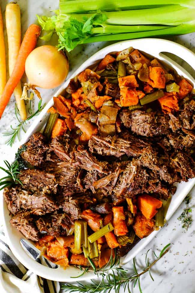 Instant pot pot roast on a platter surrounded by carrot and celery overhead shot