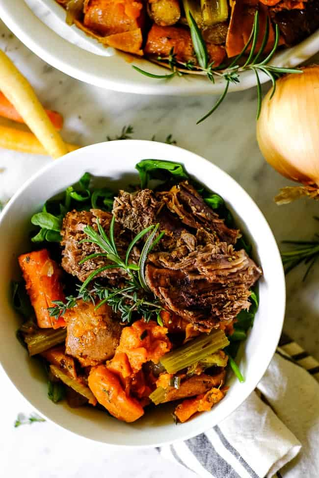 Instant Pot pot roast in a bowl with greens, sweet potato, onion, carrots, celery and fresh herbs.