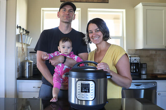 Justin and Erica Winn in the kitchen with their baby and an instant pot duo.