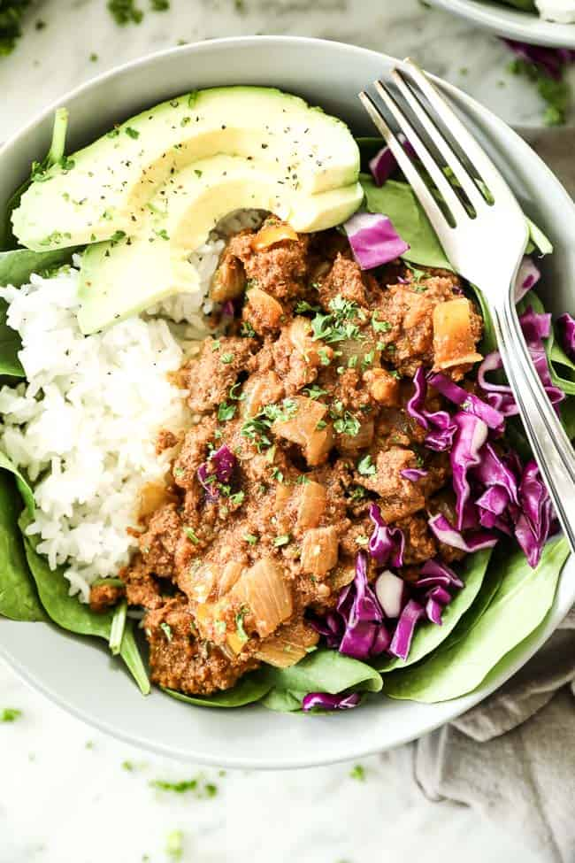Close up vertical image of instant pot sloppy joe's served in bowl with spinach, white rice, purple cabbage, parsley and avocado. Fork dug into bowl.