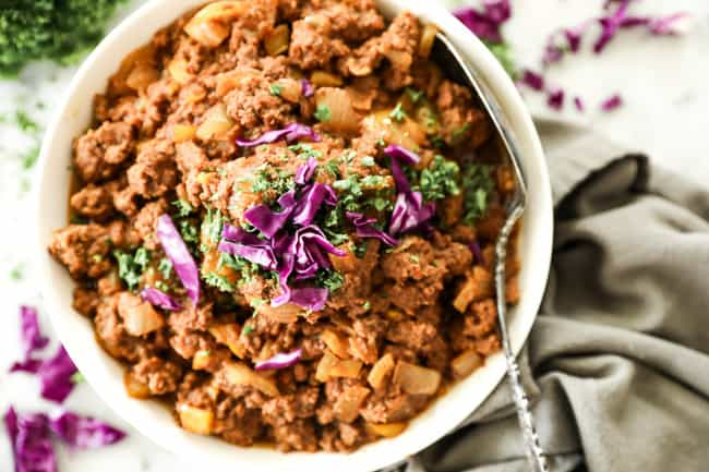 Horizontal image of instant pot sloppy joe's in a bowl with chopped parsley and purple cabbage on top. Serving spoon in bowl.