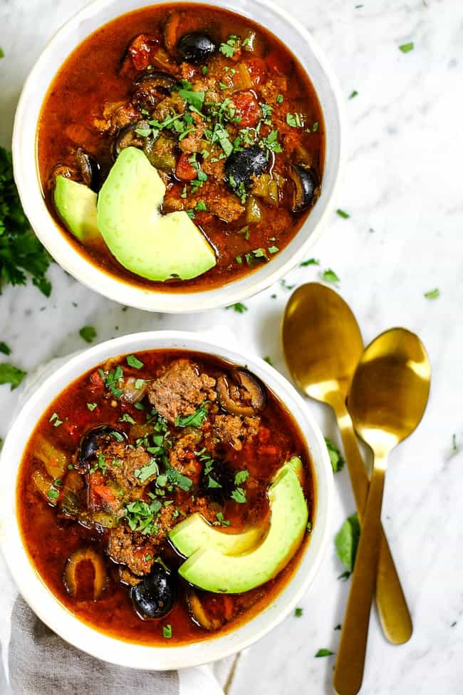 Instant Pot taco soup in two bowls with sliced avocado, chopped cilantro and two spoons.
