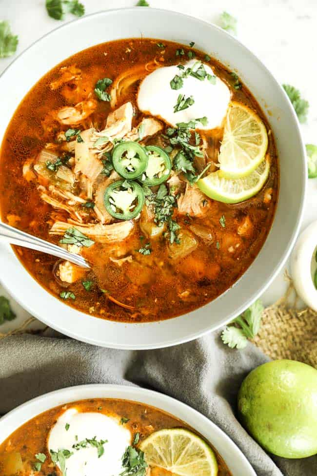 Instant pot white chicken chili vertical image with one bowl at top close up with toppings and spoon sticking out.