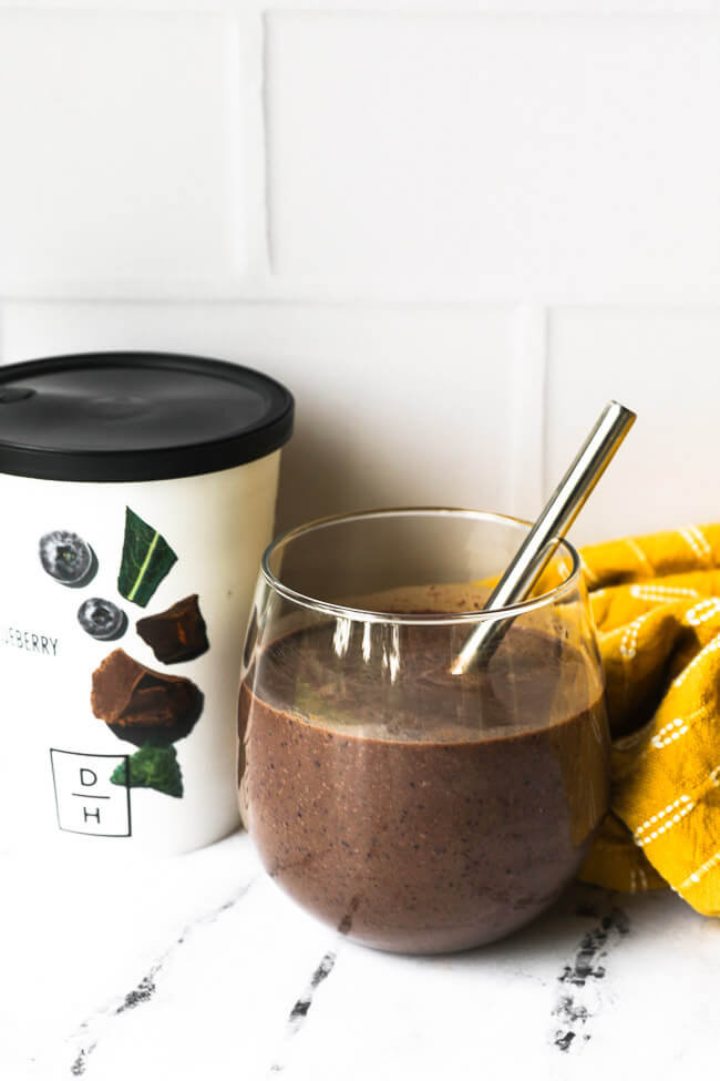 Image of Daily Harvest smoothie in a glass with a stainless steel spoon.